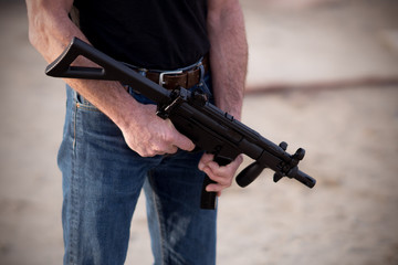 Cropped image of a man holding a rifle