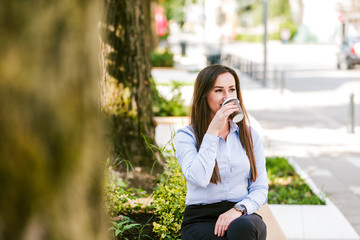 Young businesswoman drinks coffee outdoor