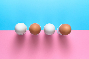 Eggs standing on egg cup on blue and pink pastel background, copy space. Boiled eggs in stand on paper background with two tone color. Healthy food concept. Easter eggs. Flat lay, top view