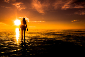 Sunset beach. Woman over sea in the sun, summer background, Baltic Sea, Poland