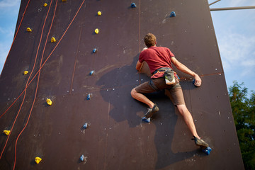 Sporty man practicing rock climbing in gym on artificial rock training wall outdoors. Young talanted slim climber guy on workout.