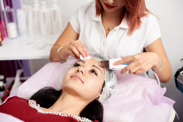 Woman cosmetologist performing an ultrasound facial peeling to a brunette patient in a beauty salon