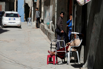 Palestinian woman sits outside her house at Shati refugee camp in Gaza City