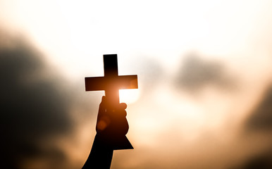 Closs up hand holding and lift of christian cross with light sunset background