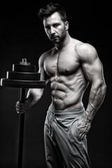 Bodybuilder standing in front of black background