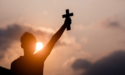 Young man hand holding and lift of christian cross with light sunset background