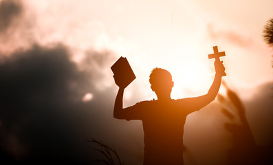 Young man hands holding holy Bible and lift of christian cross with light sunset background. christian concept