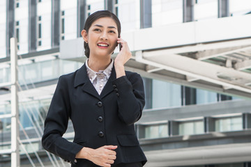 Young asian businesswoman calling on mobile phone outdoors in the downtown high building as background.