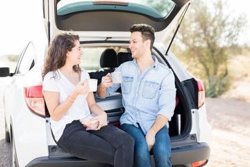 Loving couple drinks coffee sitting in car trunk