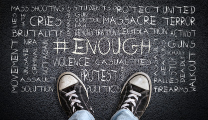 Teen in jeans and canvas shoes standing on asphalt road with # ENOUGH word cloud. Concept of social movement to protest gun violence and mass school shootings in the United States.
