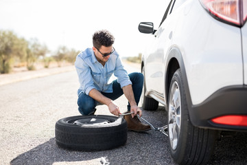 Man replacing the flat tire on the car