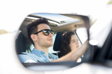 Car mirror reflection of couple on trip