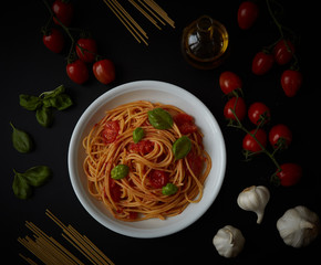 spaghetti dish with tomato sauce and basil on black background