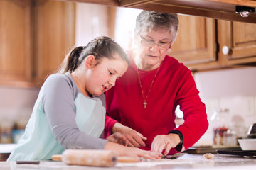 Girl and grandmother using cookie cutter on dough at kitchen counter