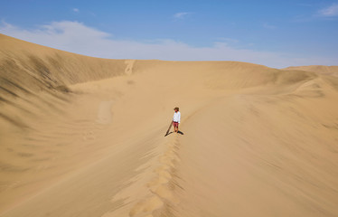 Boy with sandboard looking out over sand dunes, Ica, Peru
