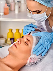 Filler injection for male face. Plastic facial surgery in beauty clinic. Man anti-aging therapy for complexion. Doctor in medical gloves with syringe forehead injects.