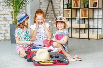 Happy children pack things in a suitcase on a journey. Concept tourism, trip, vacation, rest, sea.