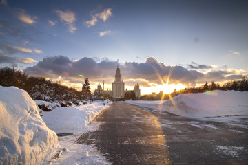 Clouds roll past Moscow State University as the sun sets on a cold evening in Moscow, Russia.