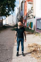 Mature male hipster standing in alleyway