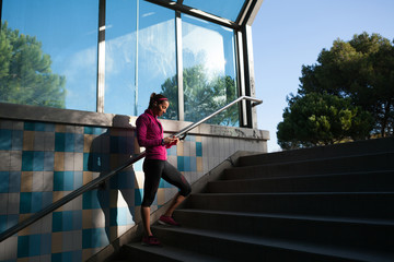 Young woman on stairway texting on smartphone