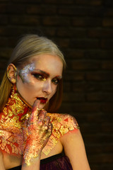 Girl with blond hair, golden foil on skin, cosmetics