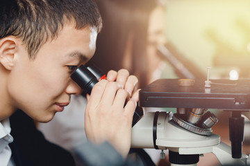 Microscope Asian student. Close-up of a man holding a microscope and analyzing. Conuept is teamwork.