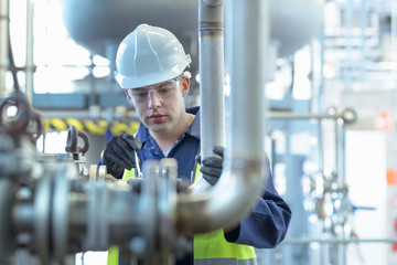 Apprentice engineer working on pipeline in industrial product facility