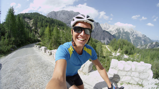 SLOW MOTION: Awesome selfie of happy man riding bicycle through the mountains.
