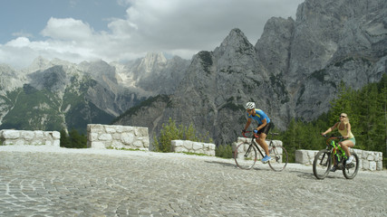 Happy active female catches up to athlete training on his bicycle in mountains.
