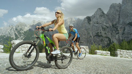 Blonde haired woman on high tech electric bike overtakes male athlete training.