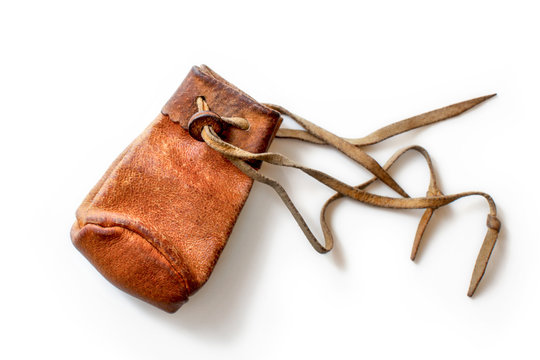 Small old worn brown leather coin pouch, isolated on white background.