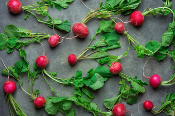 Fresh Raw Ripe Red Radishes with Green Leaves Scattered on Black Concrete Stone Background. Top View Flat Lay. Vibrant Colors. Creative Image Template for Website Banner.