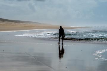 einsamer Mensch wandert am endlosen Sandstrand in der Brandung