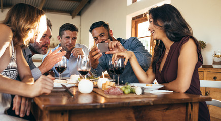 Friends at dinner party looking pictures on smartphone