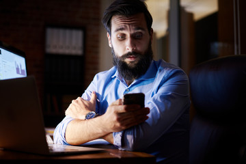 Young businessman looking at smartphone at office desk at night