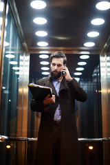 Young businessman in elevator making smartphone call