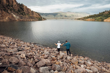 Couple walking on rocks beside Dillon Reservoir, elevated view, Silverthorne, Colorado, USA