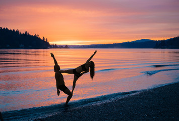 Couple practising yoga on beach at sunset