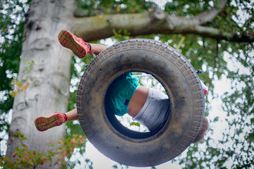 Low angle view of boy playing on tyre swing in garden