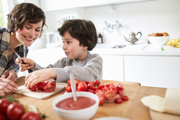 Mother and son preparing food in kitchen