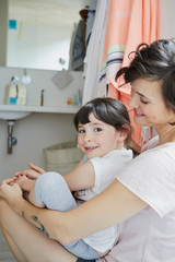 Mother and daughter sitting together in bathroom, smiling