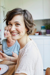 Portrait of mid adult woman at dinner table, smiling