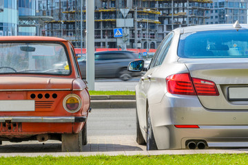 Rear view of two cars of different eras standing side by side in the city. The concept of technology development