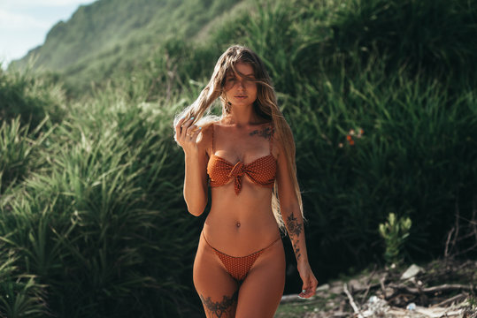 Lovely blond girl with perfect elegant body and tattoo on her leg and breast posing in red swimsuit at the beach with tropical green trees at background. Pretty Woman with long hair outdoors. Concept