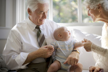 Happy grandparents holding their baby grandchild.