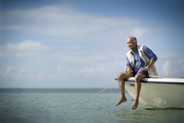 Mature man sitting on the edge of a boat fishing.