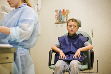 Boy sitting in chair at dental clinic
