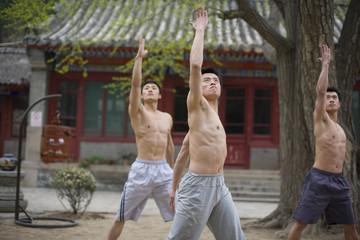 Three teenage boys practicing martial arts outside.