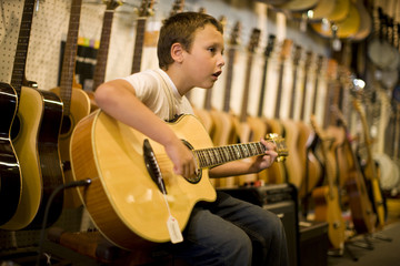 Young boy strumming an acoustic guitar inside a music shop.
