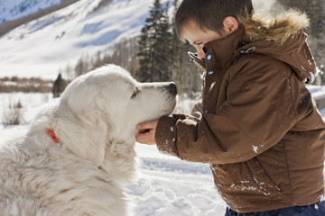 Young boy looking at his dog while playing outside in the snow.